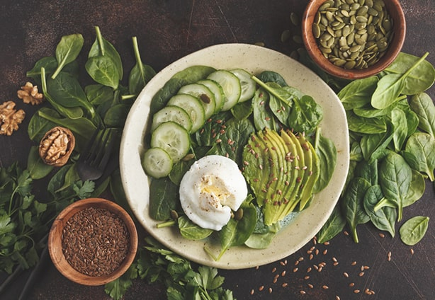 Green salad with spinach, avocado, egg, flax and pumpkin seed. Food background. Detox Vegetarian Healthy Food Concept. Top view, copy space.